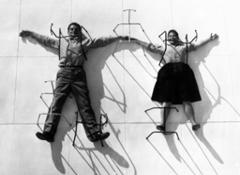 03. The World of Charles and Ray Eames. Charles and Ray Eames posing with chair bases ∏ Eames Office LLC