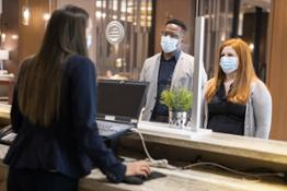 Global-CHICO-front-desk-agent-behind-safety-glass-with-facemask-checking-in-two-guests-with-facemasks v2